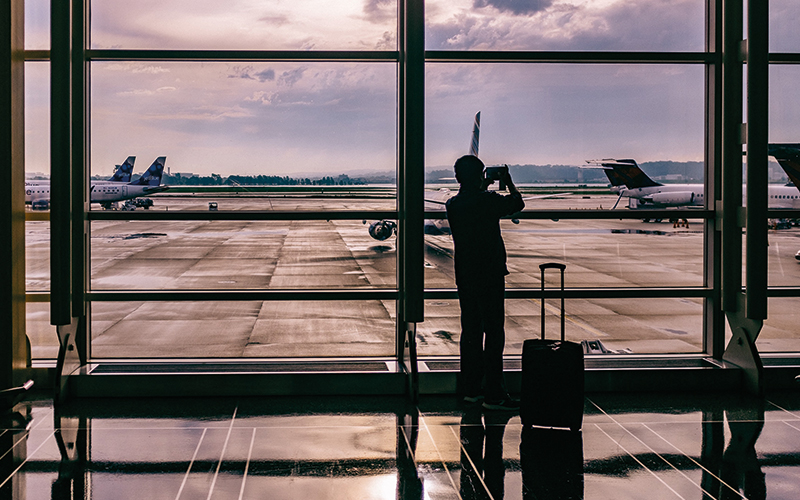Man taking photo of planes at airport