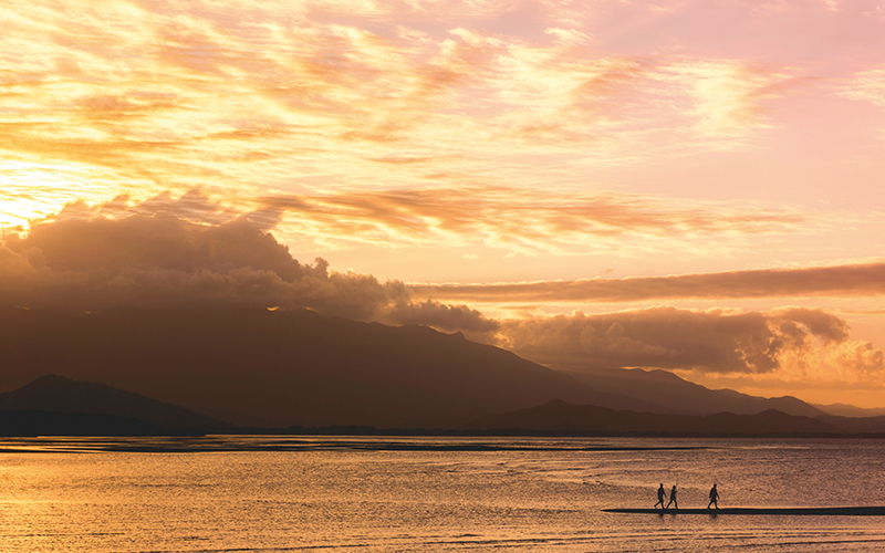 Three people walking by the water at sunset