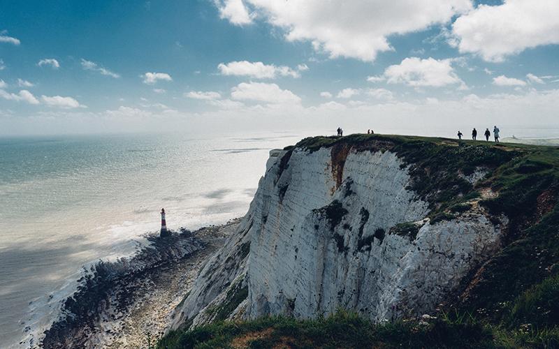 people walking along a cliff