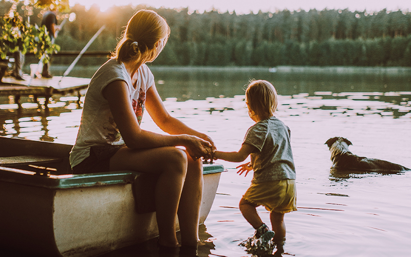 Mother, child and dog looking out over the water