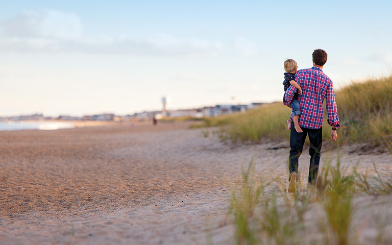 Father and son walking on the sand
