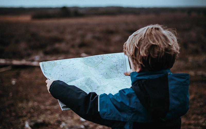 Little boy reading map