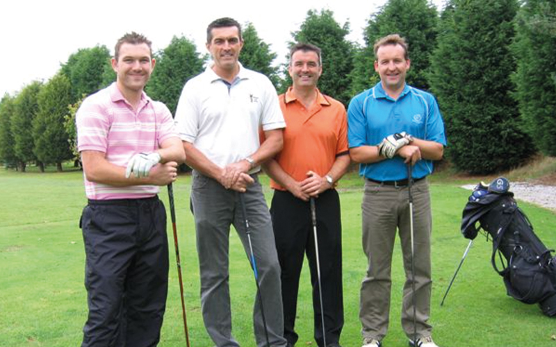 Men posing with golf clubs