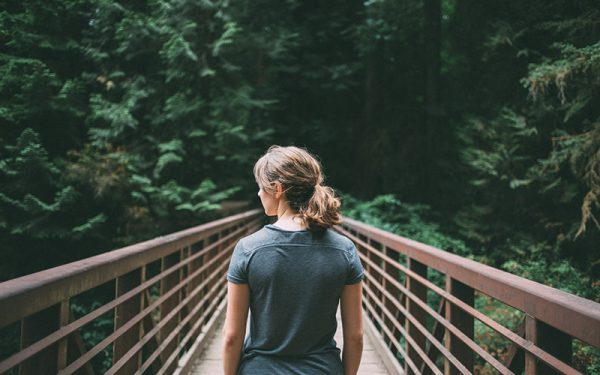Woman looking out on a bridge in the forest