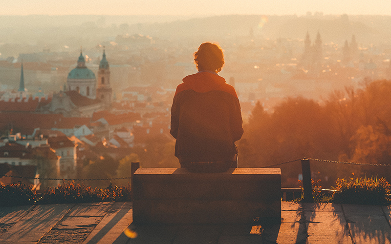 Man sat on bench looking out over city