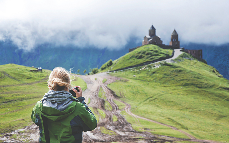Woman taking a photo of castle on the hill