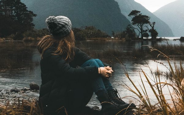Woman sat looking out over water