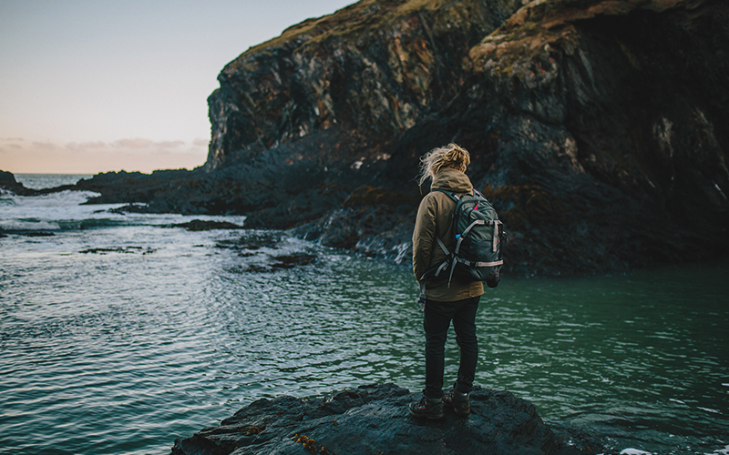 Woman standing on rock looking at water