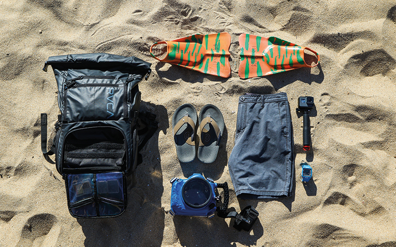 Clothes and backpack items on the sand