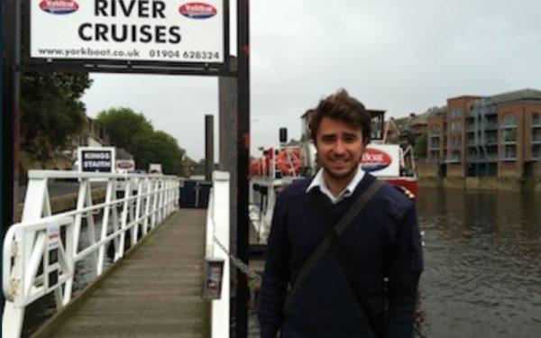 Man taking photo next to York river cruises sign
