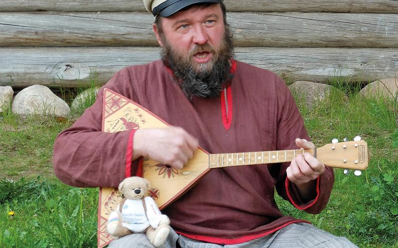 Man playing guitar with Rainbow Bear