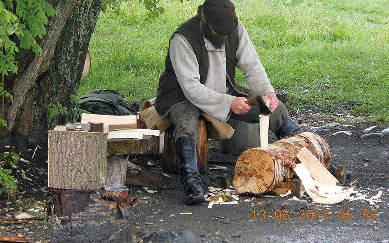 Man sat chopping logs