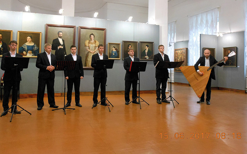 Choir singing and man playing traditional instrument