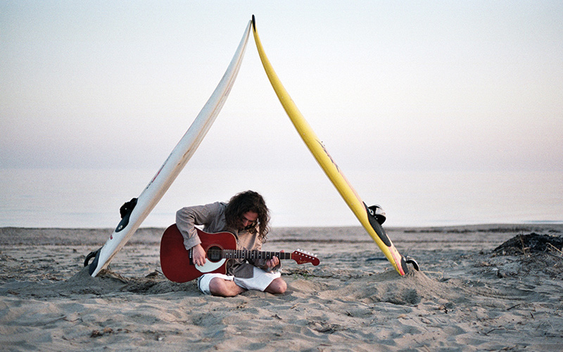 Playing guitar on beach under surf boards