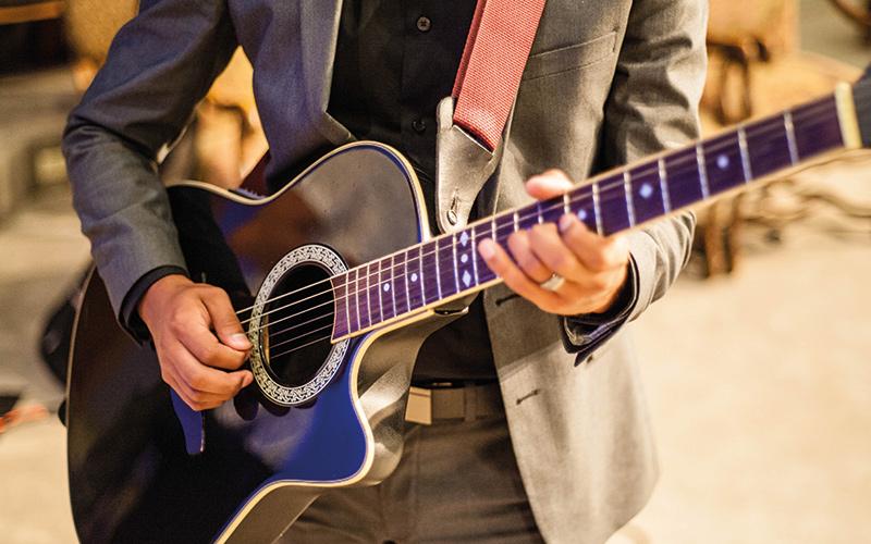 Man playing purple guitar
