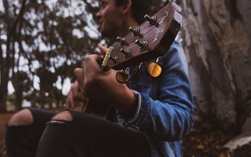 Person playing guitar in the woods