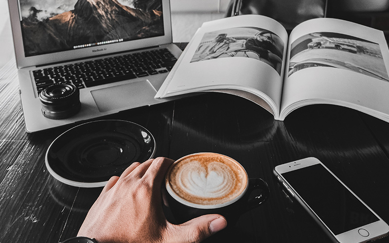 Person drinking coffee on laptop and book