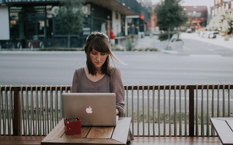Woman sat on laptop outside