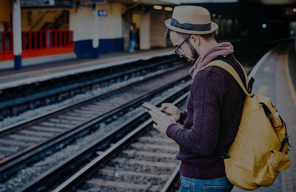 Man looking at phone on train platform