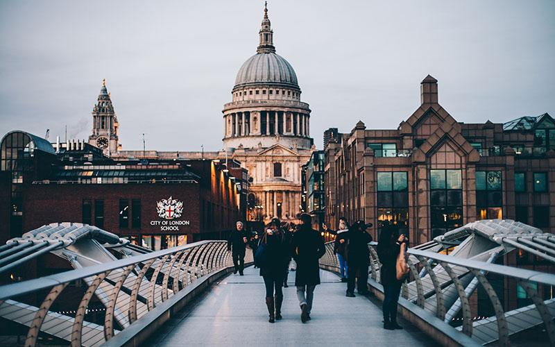 People walking along bridge in London