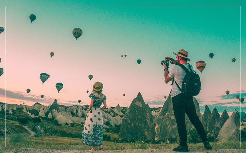 Man taking photo of woman looking at hot air balloons